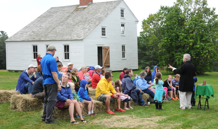 Magician Robert Olsen performs during Pettengill Farm Day. Stewards of the historic farmhouse, known for its etched murals, are dealing with an infestation of powderpost beetles.