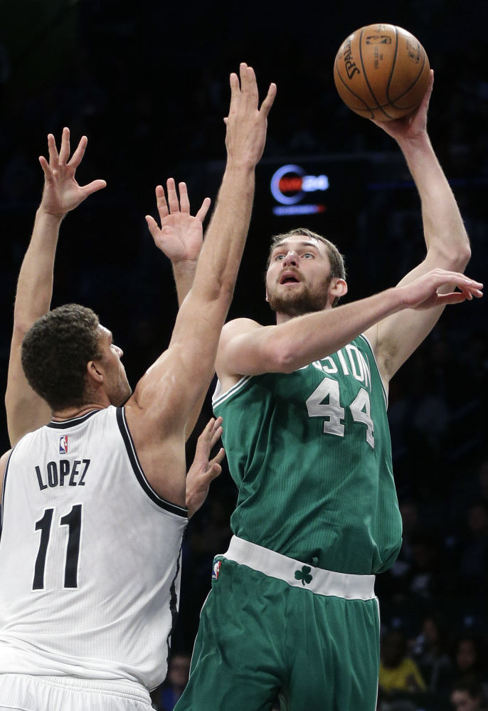 Boston's Tyler Zeller, right, takes a shot while being defended by Brooklyn's Brook Lopez on Sunday in New York. Lopez scored 23 points and the Nets won 111-101.