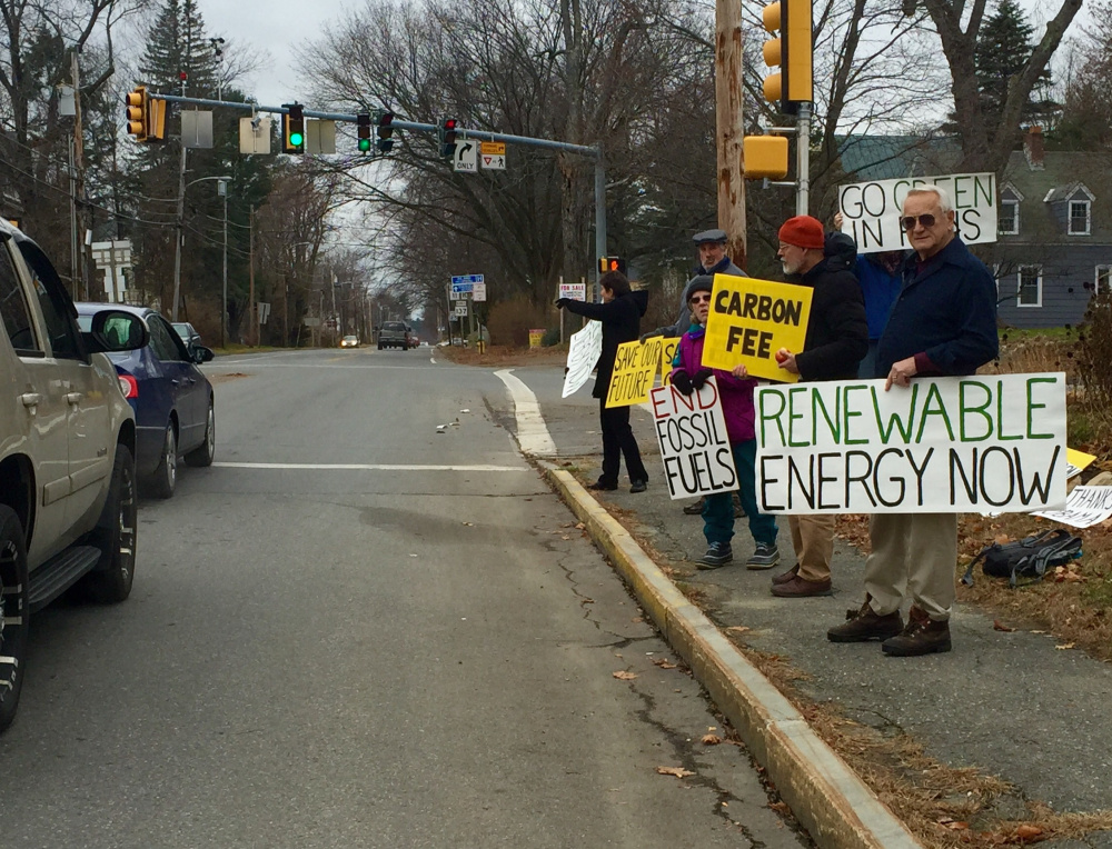 Members of 350 Central Maine demonstrate along Silver Street in Waterville in front of the Universalist Unitarian Church to promote climate change awareness.