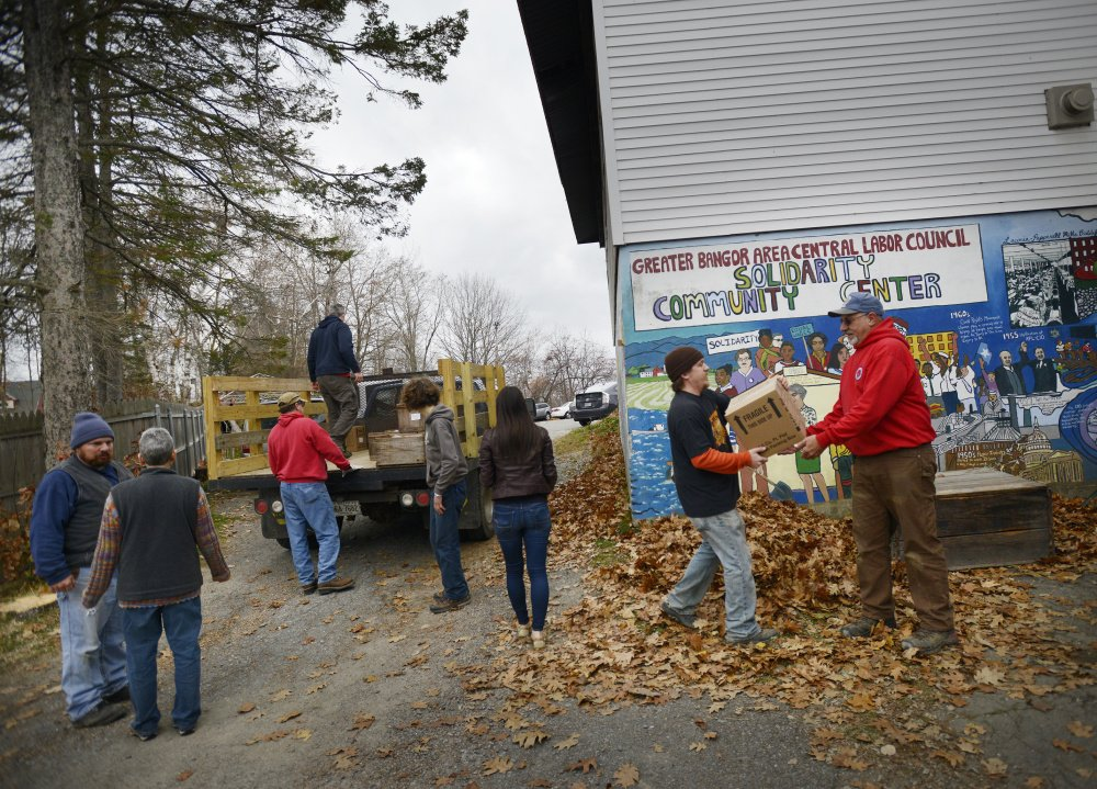 Solidarity Harvest volunteers carry apples for Thanksgiving baskets into Solidarity Center in Brewer on Thursday. The nonprofit bought 5,900 pounds of produce from 30 Maine farms.