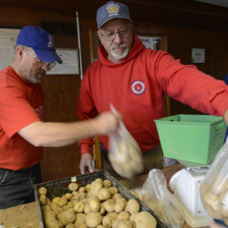 Rory Devine of Herman and Kelly Jordan of Ellsworth, both with Local 2327 IBEW, pack potatoes for Thanksgiving baskets on Thursday for Food AND Medicine, a Brewer nonprofit. Shawn Patrick Ouellette/Staff Photographer