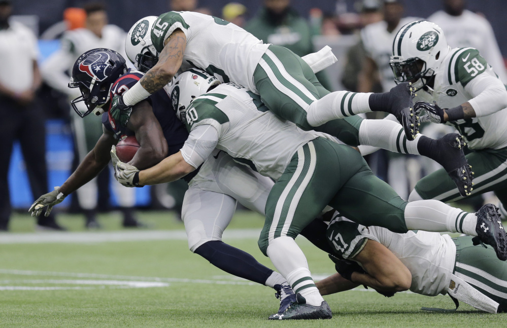 Houston receiver Keith Mumphery is stopped by Rontez Miles, top, and Tommy Bohanon of the Jets during Sunday's game in Houston. The Texans won, 24-17.