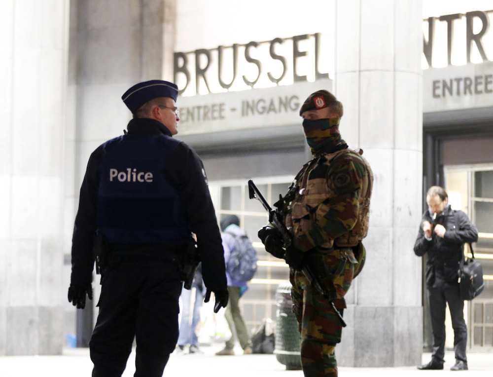Belgian police officers check in with each other in front of the central station in downtown Brussels on Monday. The capital was in its third day of lockdown, with schools and underground transport shut and more than 1,000 security personnel deployed across the country.