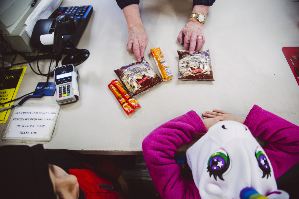 Clerk Jim Wickham checks out customers at Mellen Street Market in Portland on Monday. A new state proposal is asking for a federal waiver to allow the department to ban purchase of junk food with food stamps.