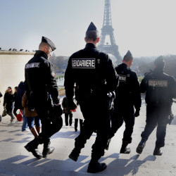 French gendarmes patrol near the Eiffel Tower in Paris on Monday. There are none of the usual long lines to ascend the iconic tower and ticket sales to Paris' major museums have also plummeted after terrorist attacks in the city.