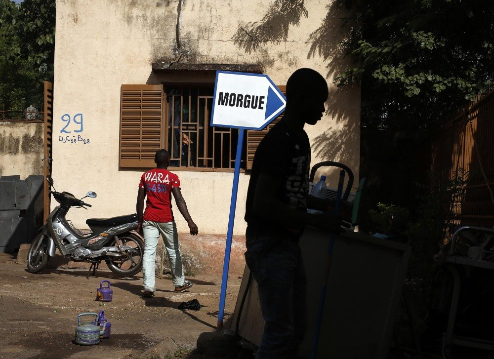 Hospital workers walk outside the morgue in Bamako, Mali where two heavily armed men shot up a hotel in the capital city last Friday, killing 19 people. State media showed photos of the dead attackers Monday as officials seek information.