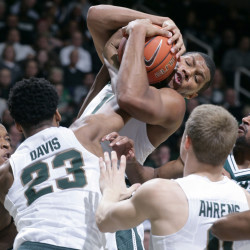 Michigan State's Marvin Clark Jr. pulls down a rebound over Eastern Michigan's Jordan Nobles, left, and Jodan Price, right, during the Spartans' 89-65 win Monday at East Lansing, Michigan.