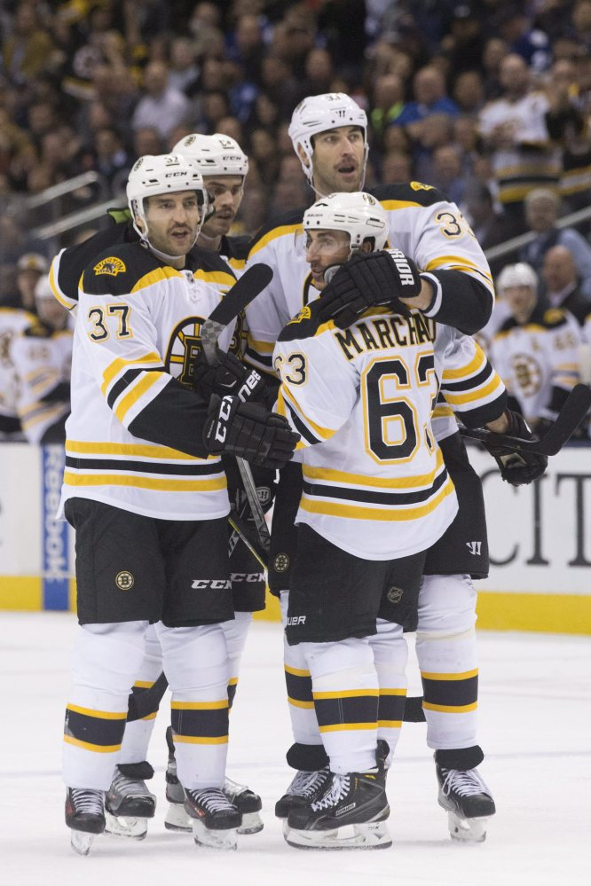 Brad Marchand is congratulated by Patrice Bergeron, left, Adam McQuaid and Zeno Chara, right, after scoring for the Bruins in the first period.