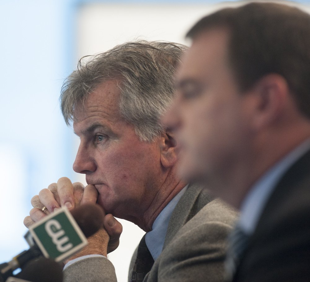 """Accompanied by Athletic Director Karlton Creech, right, Jack Cosgrove, head coach of the University of Maine's football program, announces the end of his 23-year tenure Tuesday. """"I won't miss it,"""" he said."""