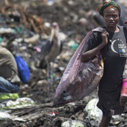 Agnes Njoki, 17, carries her daughter Shantel Akinyi, 2, as she works scavenging for plastic at the garbage dump in the Dandora slum of Nairobi, Kenya.
