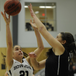 BRUNSWICK, ME - NOVEMBER 24: Bowdoin #21, Ally Silfen, puts up a rebound over the defense of UNE #11, Alicia Brown, as Bowdoin hosts UNE in Women's College basketball. (Photo by)