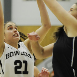 Ally Silfen of Bowdoin puts up a rebound Tuesday night while defended by Alicia Brown of the University of New England during UNE's 66-46 victory at Bowdoin.