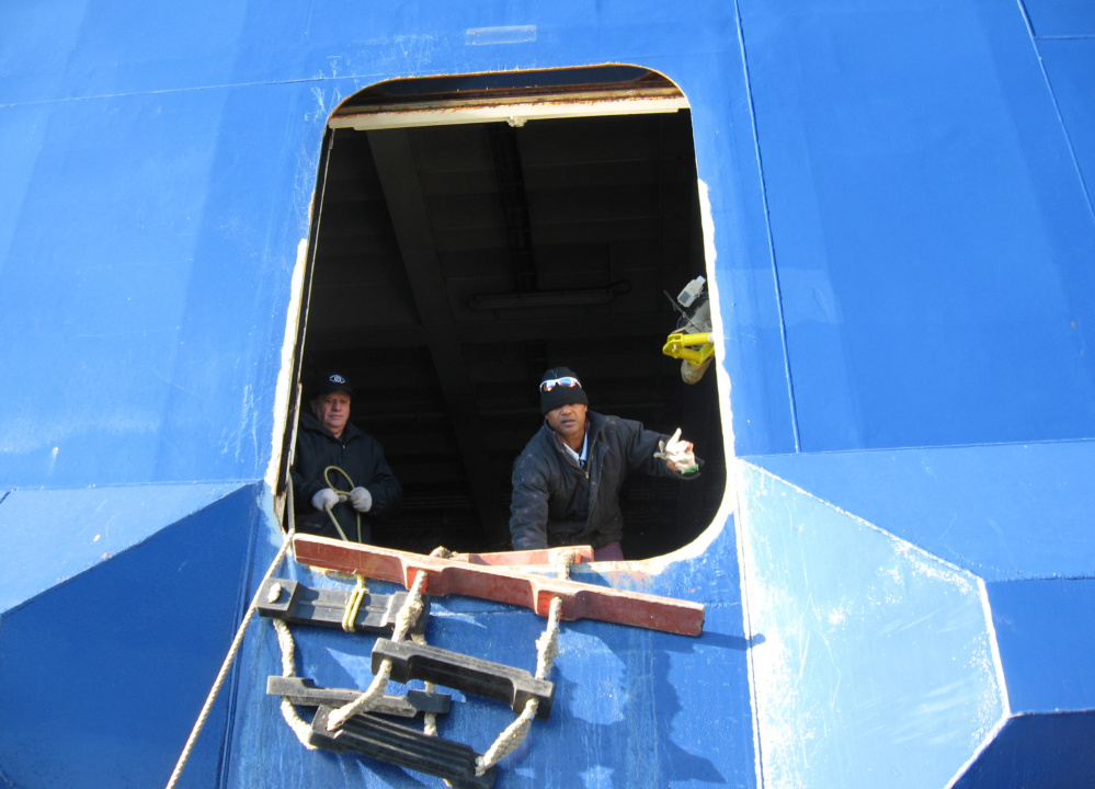 Crew members aboard the Nova Star on Wednesday receive two pallets of food supplies delivered by boat. The vessel is anchored in Portland Harbor near Fort Gorges.