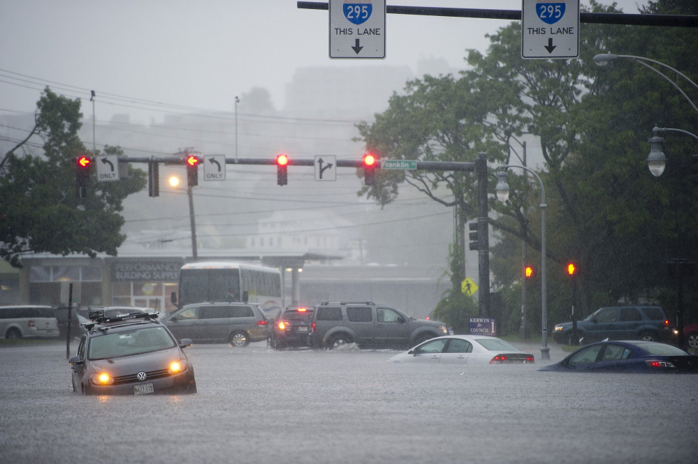 Disabled cars sit in high floodwaters at Franklin and Somerset streets in Portland during a deluge in September that coincided with a king tide.