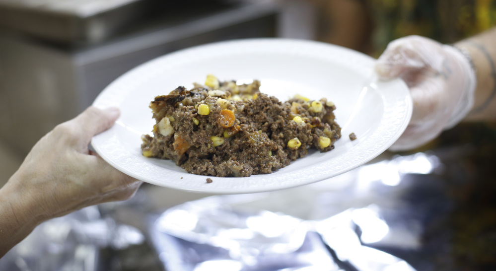 A plate of shepherd's pie made with venison and moose meat is served at a church dinner in Portland. State officials laud hunters for donating game meat to food banks and other charities.