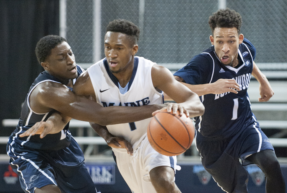 UMaine's Aaron Calixte brings the ball up the floor with pressure from Longwood's Bryan Gee, left, and Leron Fisher on Wednesday at the Cross Insurance Center in Bangor. UMaine won, 92-82.
