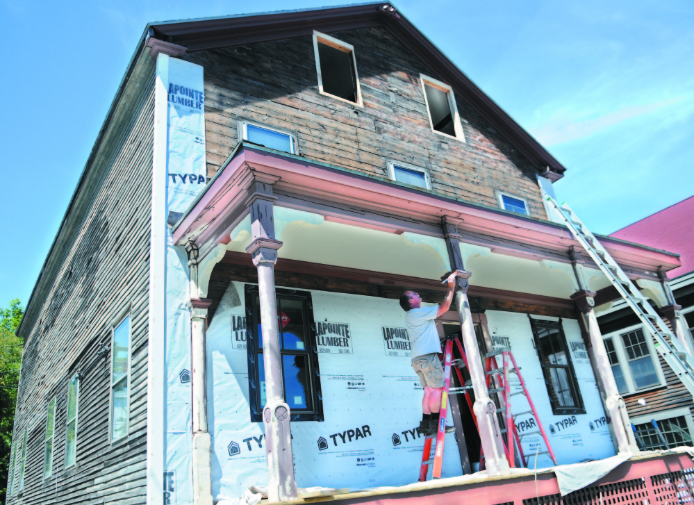 Mark Curtis, of Guyon & Sons Painting, coats trim on the porch of the former Hallowell Granite Works office building in 2013 in Hallowell. The renovation of the building, owned by Jim Duncklee and Ken Knott, was honored by Maine Preservation last week, one of 16 in the state recognized by the organization.