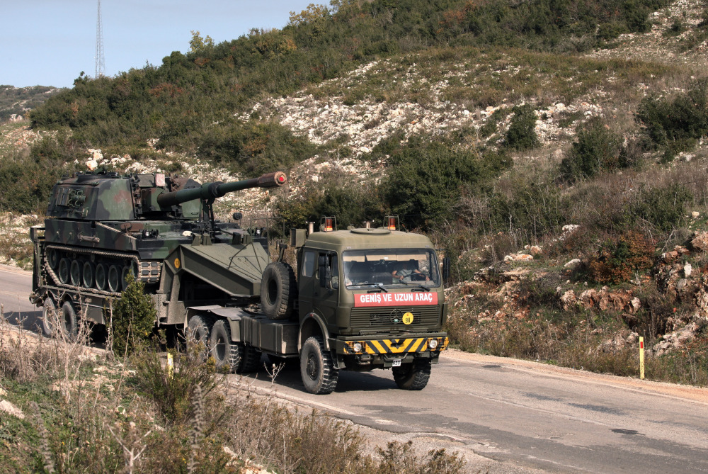 "A Turkish army truck loaded with a self-propelled gun heads to the Syrian border near Yayladagi, Turkey, on Wednesday. Prime Minister Ahmet Davutoglu is seeking to reduce tensions with Moscow, saying that Russia is Turkey's ""friend and neighbor"" and insisting relations cannot be ""sacrificed to accidents of communication."" The Associated Press"