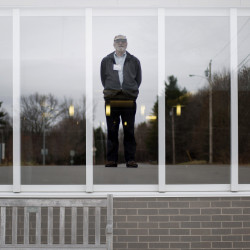 David Clark poses on a road in Augusta, with the image superimposed on a window at the Harold Alfond Center for Cancer Care, where his late wife was treated for the disease. Since then, Clark has logged about 30,000 miles driving cancer patients to their appointments. Gabe Souza/Staff Photographer