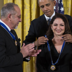 Emilio Estefan watches President Obama present the Presidential Medal of Freedom to his wife, Gloria Estefan, at the White House Tuesday. Both Estefans got medals.