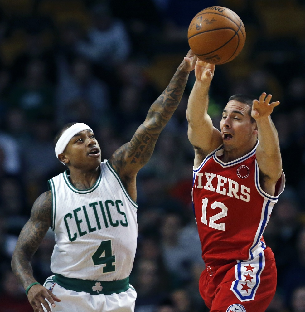 Philadelphia's T.J. McConnell passes as Isaiah Thomas defends in the first quarter. Thomas led a late rally that pushed the Celtics to an 84-80 win over the winless 76ers.