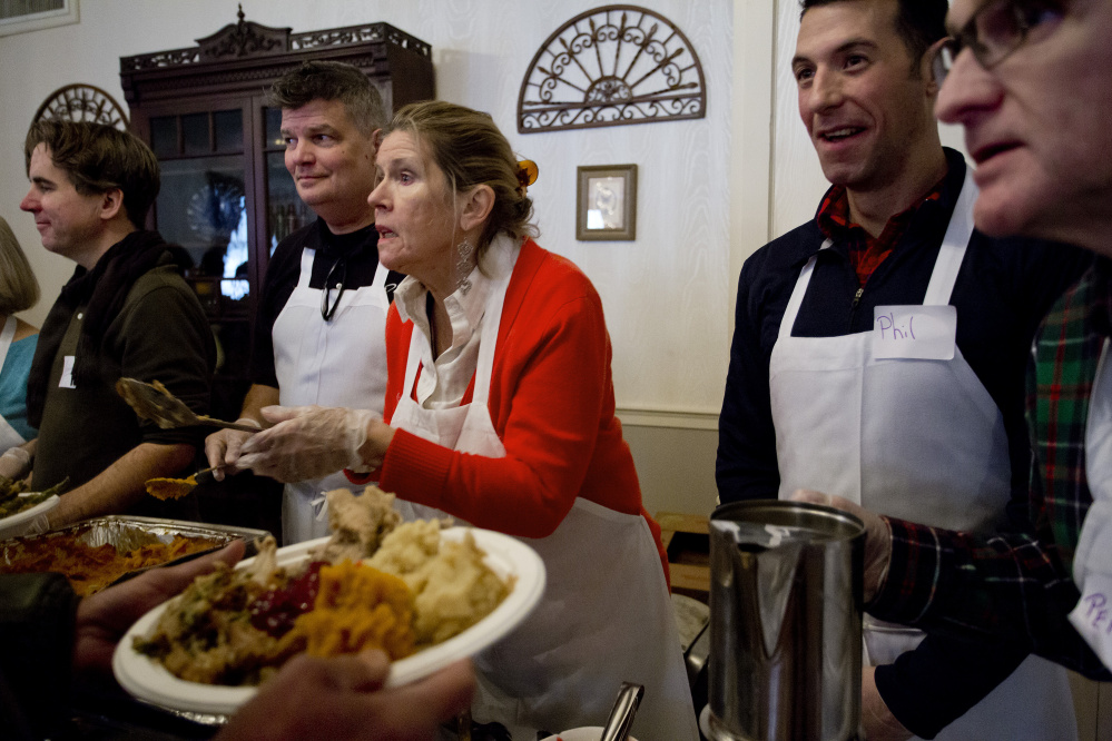 Volunteers, from left, John Monahan, Michael Quint, Marlies Heitmann, Phil Allard and Perry St. Louis serve a Thanksgiving meal at the Portland Club during last year's Wayside Food Programs' annual community dinner.