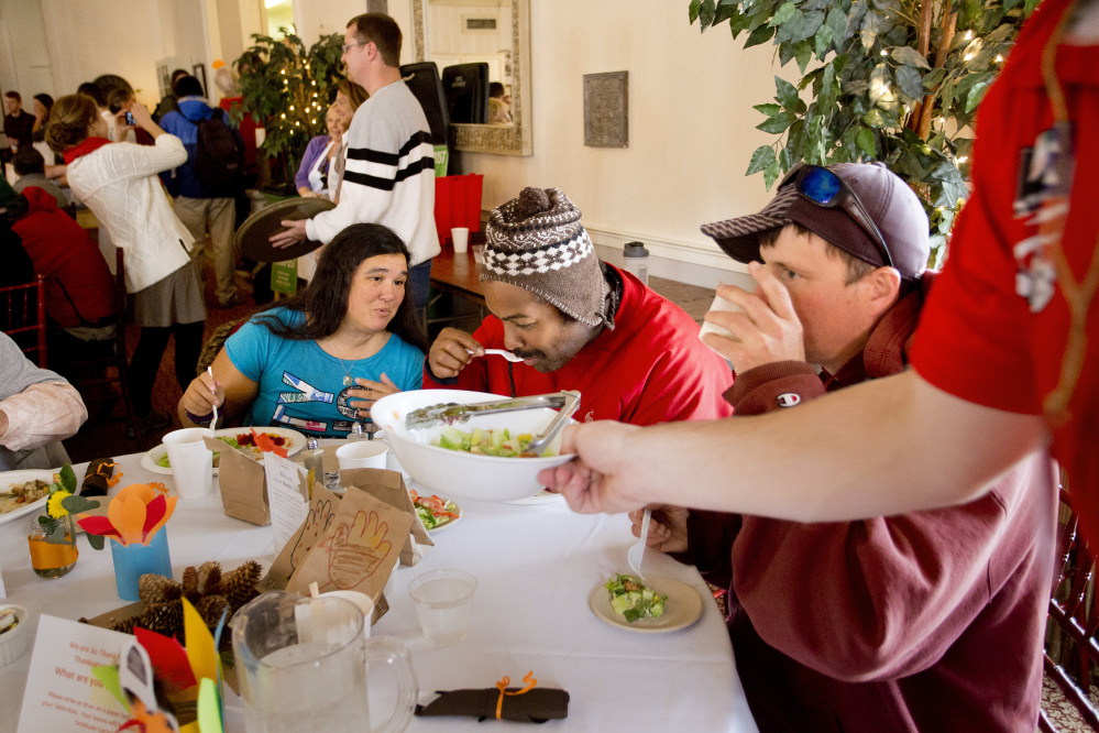 Donna Gagne, Kenny Bringle and William Dornermann, all of Portland, eat their Thanksgiving dinner as volunteer Evan Milkowski clears a bowl of salad from the table.