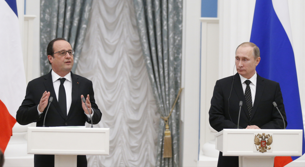 Russian President Vladimir Putin looks on as French President Francois Hollande speaks at a news conference Thursday after their meeting in Moscow. The two agreed to share information and cooperate on selecting Islamic State targets.