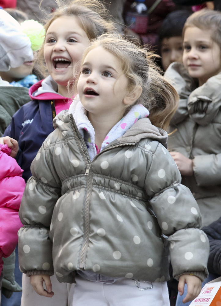 Children react as Santa Claus passes on a large float to cap off Thursday's parade.