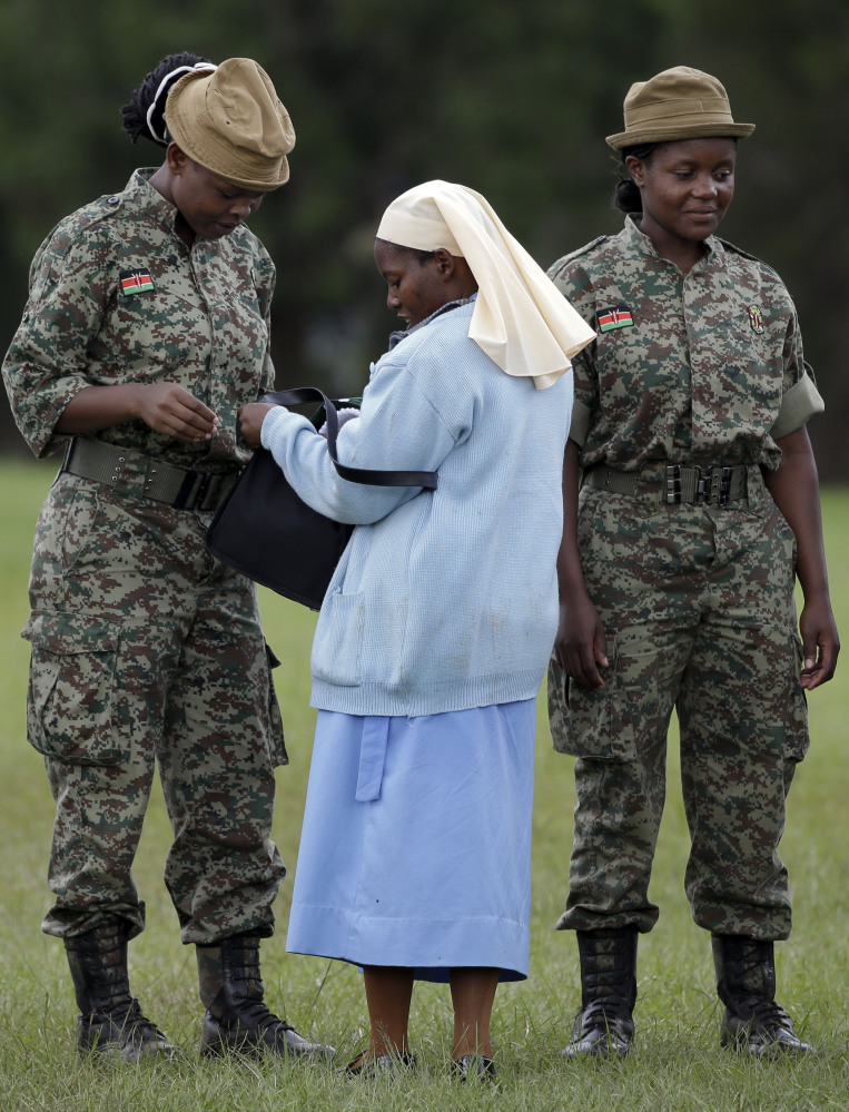 Below, a nun has her bag checked by army soldiers as she arrives to attend a meeting held by the pope.