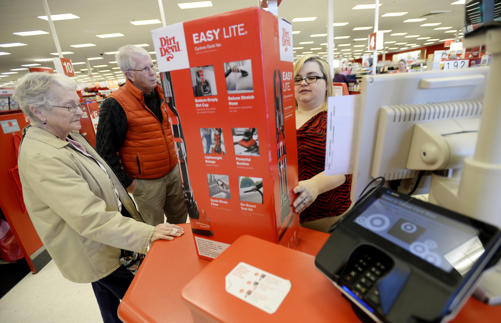 Cashier Danielle Johnson checks out Lorraine Libby of Scarborough and Gordon Smith of Cape Elizabeth at Target, which has taken an extra step in payment security by offering cards with microchips and requiring cardholders to enter a PIN.