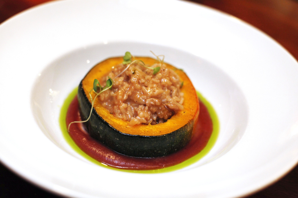 Walnut risotto-stuffed long pie pumpkin with savory cranberry apple puree and herb oil.