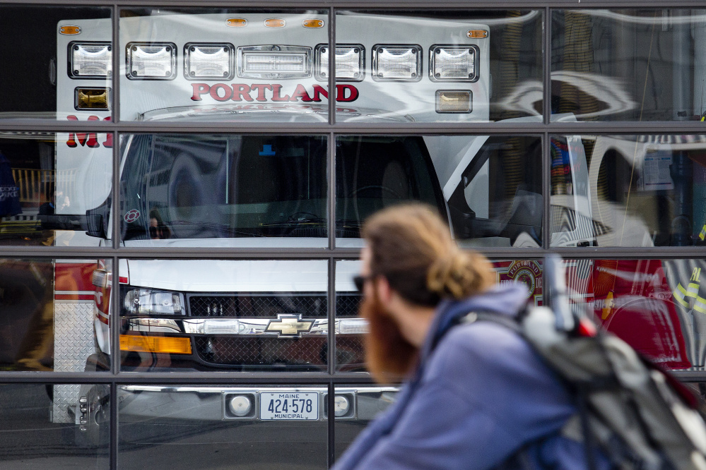 A bicyclist rides past the ambulance at Munjoy Station on Friday, when the ambulance was back in service from 8 a.m. to 8 p.m.