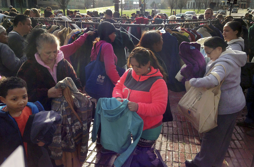 "People choose free winter coats off racks on the Statehouse lawn during the ""Buy Nothing Day"" on Friday at Providence, R.I. For 19 years, the annual exchange has provided warm coats while trying to counter the effects of consumerism."