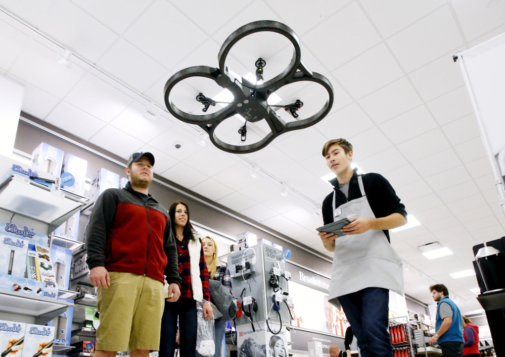 Cary Grimmett, left, and Kaylei Combs watch as Brookstone employee Dylan Crovo demonstrates the flying capabilities of a drone at the Maine Mall in South Portland.