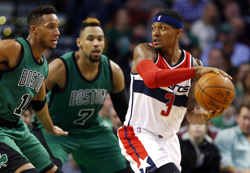 The Wizards' Bradley Beal looks for an opening around the Celtics' Jared Sullinger (7) and Evan Turner in the second quarter. Sullinger piled 18 points and 15 rebounds in just three quarters.