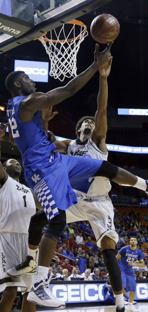 Kentucky forward Alex Poythress, center, shoots as South Florida forward Chris Perry, left, and Nehemias Morillo defend during the No. 1 Wildcats' 84-63 win on Friday.