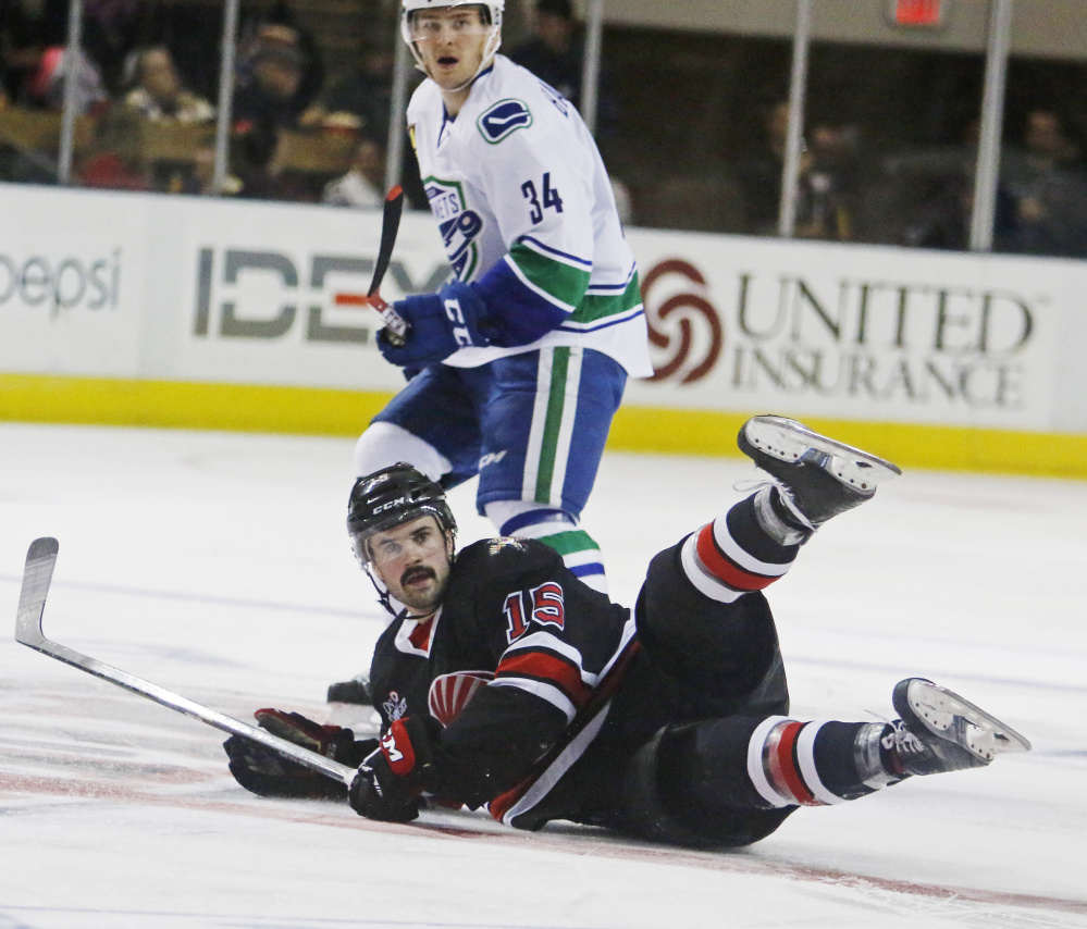 John McFarland of the Portland Pirates hits the ice Friday night in front of Carter Bancks, who scored two goals for the Utica Comets in a 4-1 vicotry at the Cross Insurance Arena. The teams meet again Saturday night.