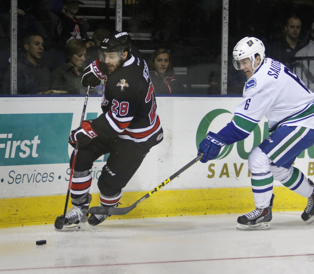 Wade Megan of the Portland Pirates moves the puck along the boards while being pressured by Ashton Sautner of the Utica Comets during the second period.