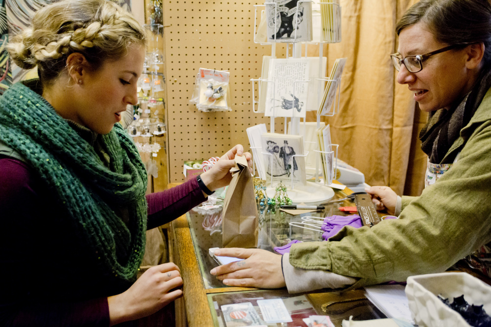 Emily Stout of Worcester, Mass., left, finishes a transaction with Diane Toepfer at Ferdinand in Portland on Small Business Saturday, a day created by American Express six years ago.