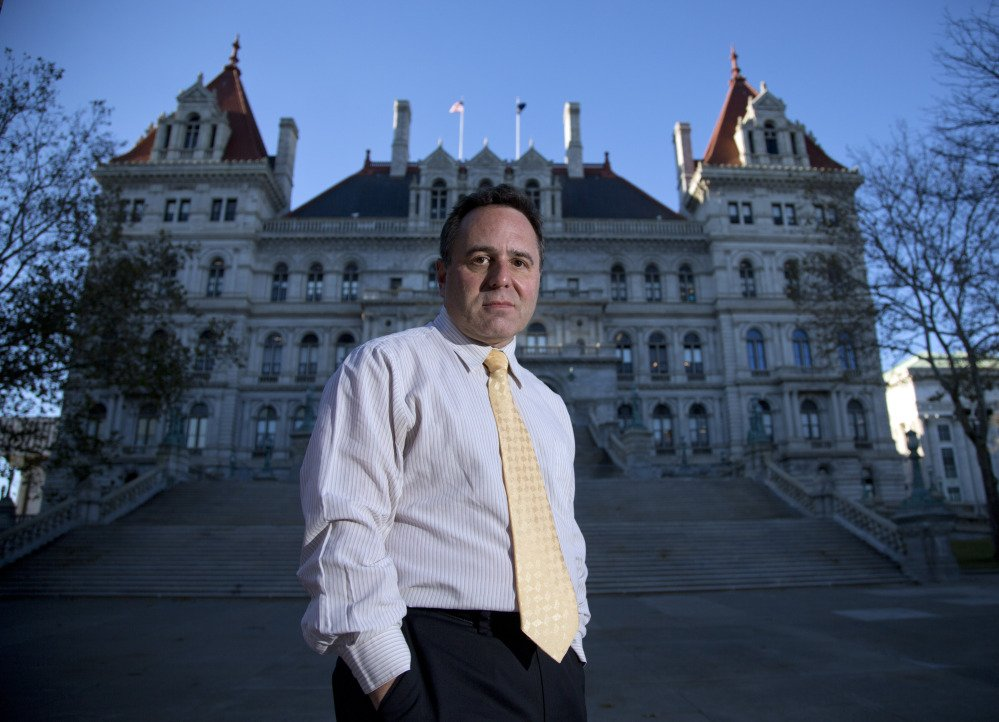 In this Nov. 23, 2015 photo, College of Saint Rose professor Bruce Roter, founder and president of the Museum of Political Corruption, poses outside the state Capitol in Albany, N.Y. Roter envisions a museum that would not only detail Albany's many political scandals but also offer some possible solutions to corruption.  (AP Photo/Mike Groll)