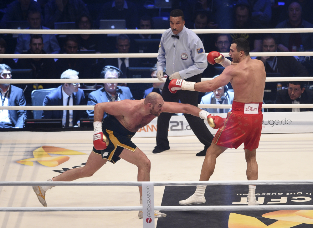 Ukraine's Wladimir Klitschko, right, and Britain's Tyson Fury exchange blows as referee Tony Weeks looks on in a world heavyweight title fight for Klitschko's WBA, IBF, WBO and  IBO belts in the Esprit Arena in Duesseldorf, western Germany, Saturday. Fury won a unanimous decision. (The Associated Press)