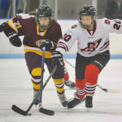 Annie Citrine of Cape Elizabeth, left, and Logan Bruns of Scarborough compete for the puck Saturday during their girls' hockey game in Saco. Scarborough remained undefeated – two wins and a tie – with a 2-0 victory.