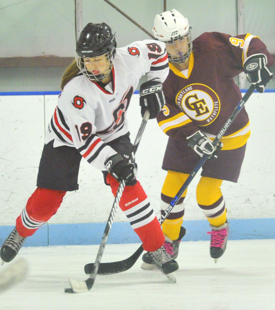 Lauren Topchik of Scarborough attempts to elude Sophie Miller of Cape Elizabeth while controlling the puck. Scarborough scored once in the second period and another into an empty net in the last minute of the game.