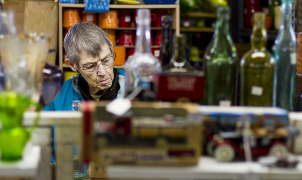 Marilyn Foster, of Westbrook, browses the shelves at Bo-Mar Hall. Items for sale included a box of (Doug) Flutie Flakes and a President Clinton Dancin' Machine.