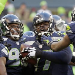 Seattle's Ahtyba Rubin, center, is congratulated after his interception in the second half of the Seahawks' 39-30 win over the Steelers on Sunday in Seattle.