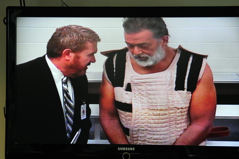 "Planned Parenthood shooting suspect Robert Lewis Dear, assisted by public defender Daniel King, appears Monday via video before Judge Gilbert Martinez in Colorado Springs, Colo. When asked if he understood his rights, Dear replied, ""No questions."""