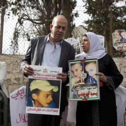 Suha and Hussein Abu Khdeir, center, parents of Mohammed Abu Khdeir, hold posters with his portrait after the reading of the verdict in his killing Monday at Jerusalem District Court. The court convicted two Israeli youths in the grisly murder of Abu Khdeir.