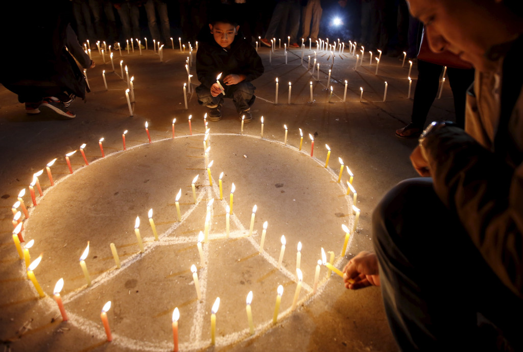 Navesh Chitrakar/Reuters @CAP.cutline:People light candles at a vigil Sunday in Kathmandu to remember the victims of the attacks in Paris, where residents remained on edge during a second day of mourning.  Navesh Chitrakar/Reuters