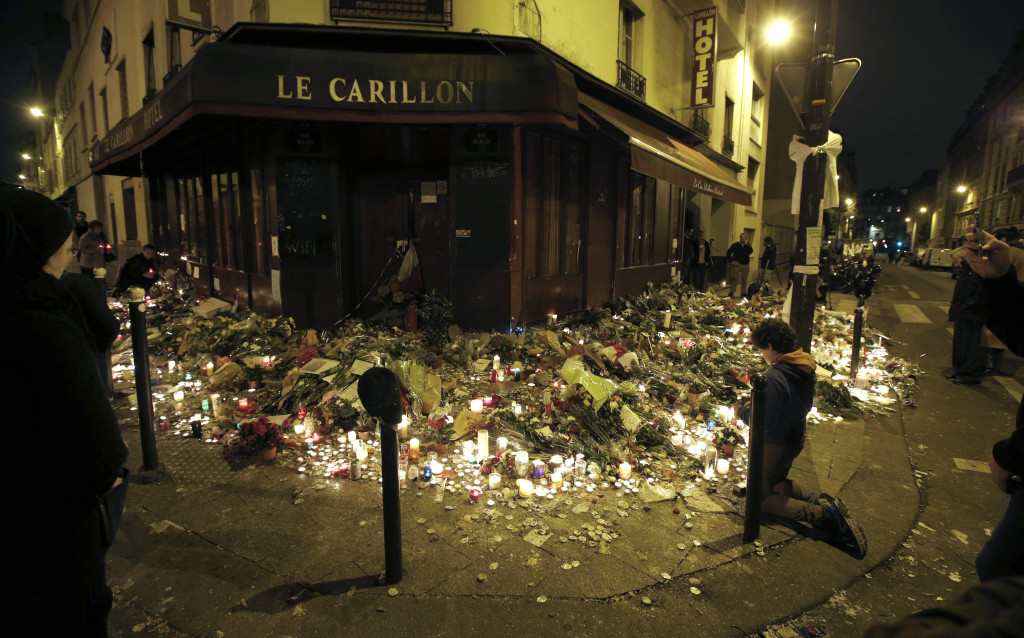 People pray Sunday outside Le Carillon restaurant, one of the attack sites where crowds have laid flowers and lit candles in memory of the 15 people killed there. At one point jittery mourners panicked and police moved in with guns drawn.  Jacky Naegelen/Reuters
